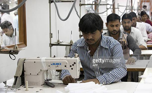 Indian labourers sew linens at the April Cornell clothing factory in Noida on the outskirts of New Delhi on October 16 2012 The April Cornell company...
