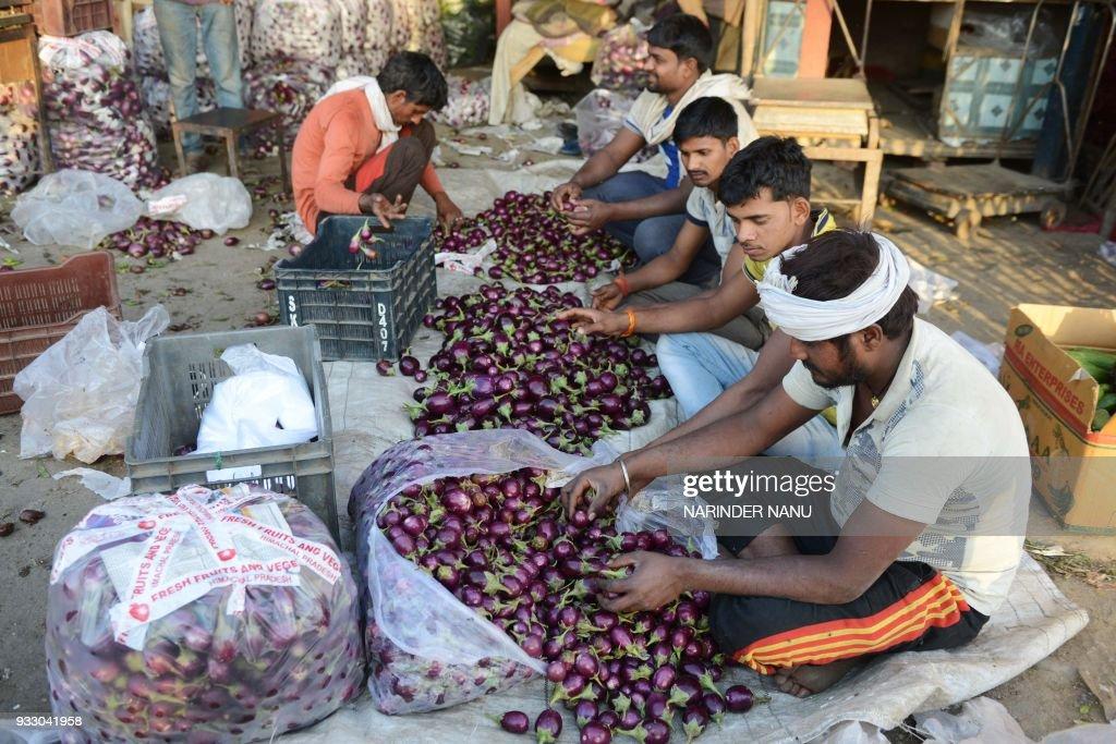 Indian labourers sort brinjal at a vegetable market in Amritsar on March 17 2018 / AFP PHOTO / NARINDER NANU
