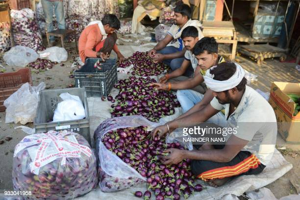 Indian labourers sort brinjal at a vegetable market in Amritsar on March 17 2018 / AFP PHOTO / NARINDER NANU