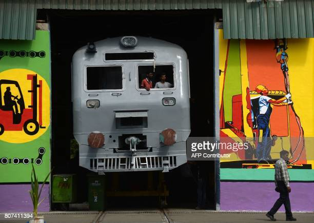 Indian labourers stand inside an Indian Railways locomotive coach at the Integral Coach Factory in Chennai on July 4 2017 / AFP PHOTO / ARUN SANKAR