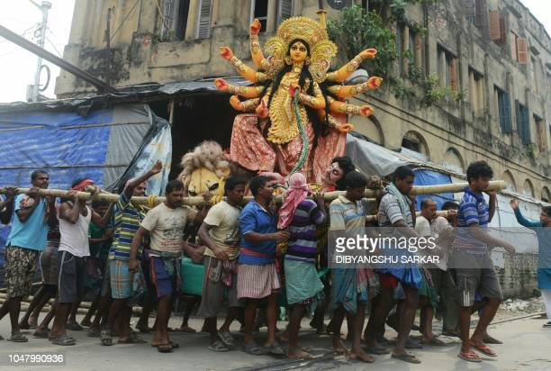 Indian labourers transport a clay statue of the Hindu goddess Durga from the artisan's village of Kumartoli to a place of worship ahead of the Durga...