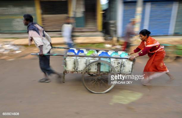 TOPSHOT Indian labourers transport canisters of drinking water to distribute to food stalls in Agartala on March 21 on the eve of World Water Day...
