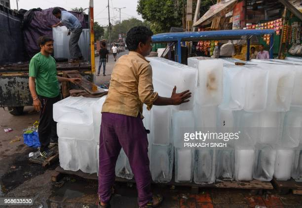 Indian labourers unload big ice blocks at a retail shop during a hot summer day in New Delhi on May 15 2018