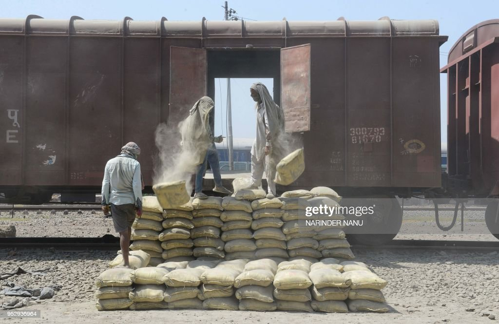 Indian labourers unload sacks of cement from a train at a railway station on the outskirts of Amritsar on April 30 ahead of the International Labour..