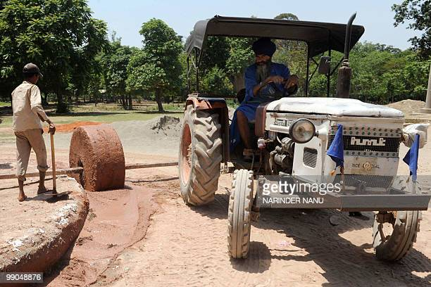 Indian labourers use a tractor and roller to spread a mixture of Chuna sand and surkhi an artificial pozzolana made by powdering burnt bricks known...