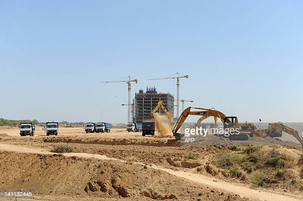 Indian labourers use heavy machinery to work on a road leading to a construction site of Gujarat International Finance Tec City GIFT City on the...