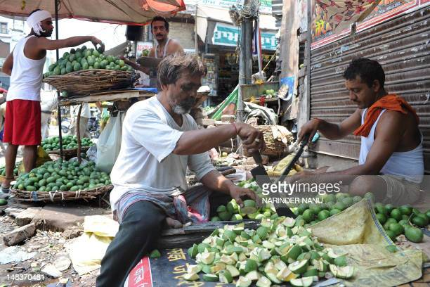 Indian labourers who earn approximately 300 to 400 Indian rupees per day cut raw mangoes which are used for pickles at the roadside in Amritsar on...