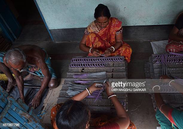Indian labourers work at a firecracker factory on the outskirts of Kolkata on October 17 2014 Hindu devotees use firecrackers while celebrating the...