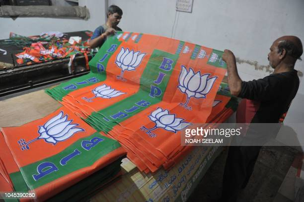 Indian labourers work at a workshop making Bharatiya Janata Party election campaign banners for the upcoming Telangana state legislative assembly...