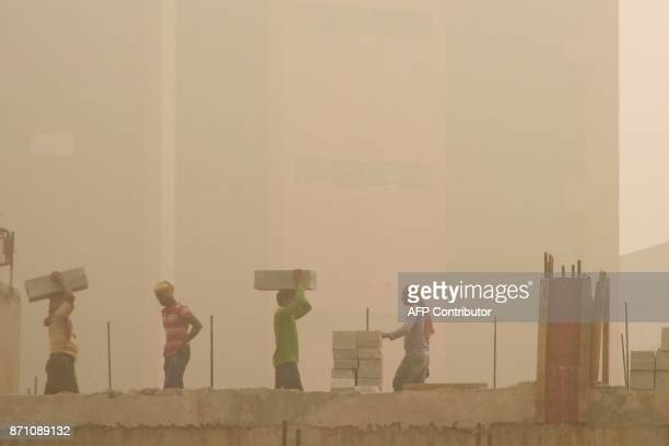 Indian labourers work on a construction site during heavy smog conditions in New Delhi on November 7 2017 New Delhi woke up to a choking blanket of...