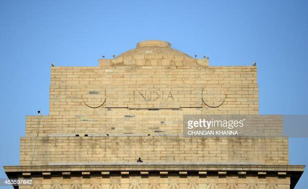 Indian labourers work on the top of India Gate in New Delhi on August 14 on the eve of Independence Day India celebrates its anniversary of...