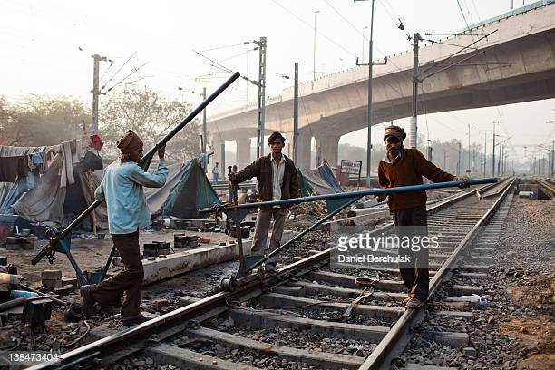 Indian labourers work on the tracks at Nizamuddin Railway Station on February 07 2012 in New Delhi India The Nizamuddin Railway Station serves as the...