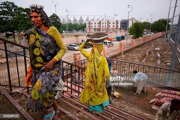 Indian labourers work to concrete a staircase on a pedestrian bridge outside of the main stadium for the approaching 19th Commonwealth Games 2010...