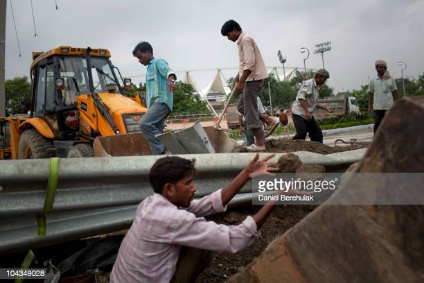 Indian labourers work to remove debris from yesterdays collapsed foot bridge at the main stadium for the approaching 19th Commonwealth Games 2010...