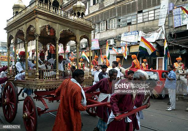 Indian labourerss pull a chariot with traditional musicians as they participate in a religious rally organised on the occasion of Mahavir Jayanti in...