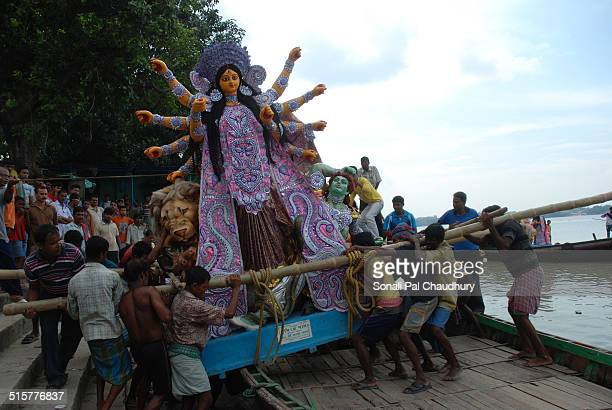 Indian labours carrying the idol Durga in a boat in Kumartuli Kolkata