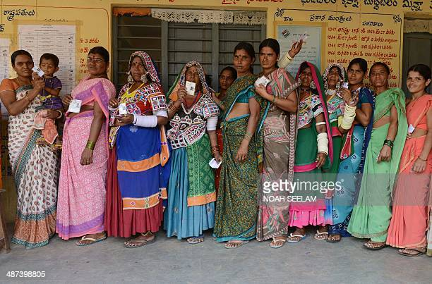 Indian lambadi tribeswomen pose for a photograph as they queue to cast their ballots at a polling station at Rangareddy on the outskirts of Hyderabad...