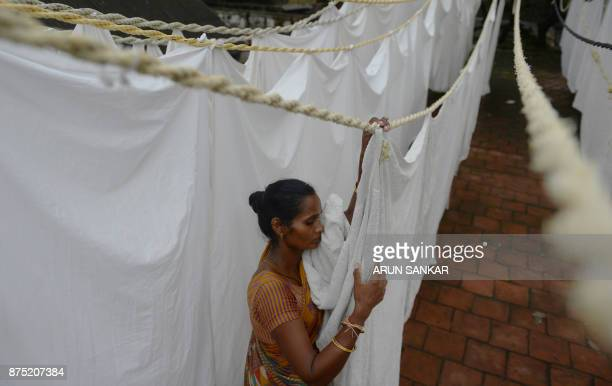 A Indian laundry worker hangs freshlywashed sheets at one of the city's oldest laundry facilities or 'dhobi ghats' in Chennai on November 17 2017 /...