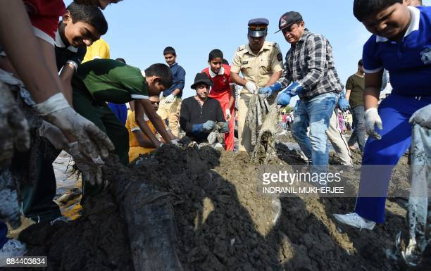 Indian lawyer and environmentalist Afroz Shah collects trash with other volunteers during a clean up drive at the Versova beach in Mumbai on December...