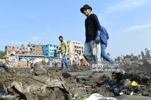 Indian lawyer and environmentalist Afroz Shah walks through heaps of garbage during a clean up drive at the Versova beach in Mumbai on December 2...