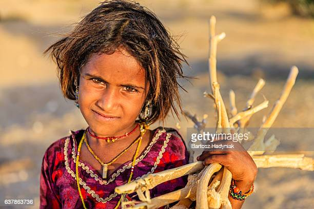 Indian little girl carrying brushwood, desert village, Rajasthan, India.