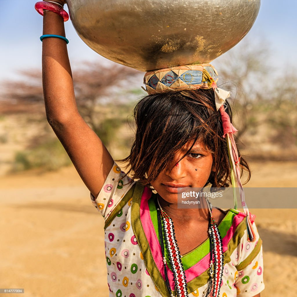 Indian little girl carrying on her head water from well : Stock Photo