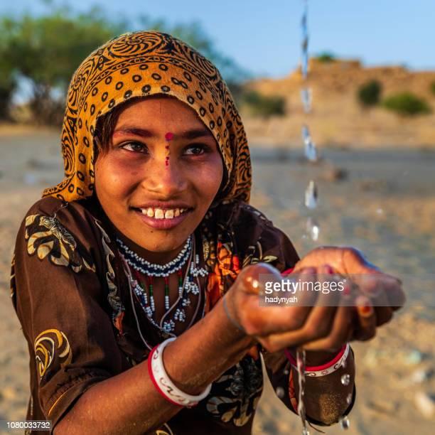 menina indiana beber água fresca, uma aldeia deserta, rajastão, índia - hinduísmo - fotografias e filmes do acervo