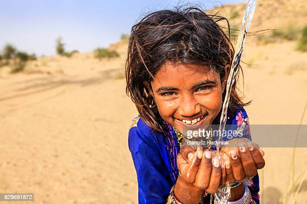 Indian little girl drinking fresh water, desert village, Rajasthan, India