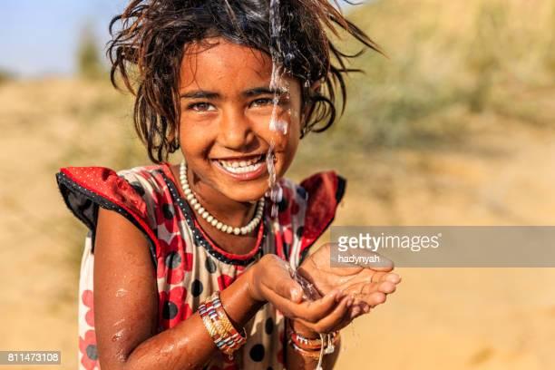 Indische Mädchen trinkt Wasser, desert village, Rajasthan, Indien