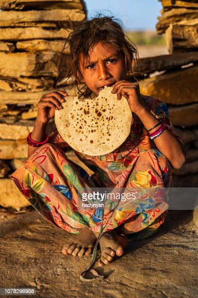 indian little girl eating chapatti, flat bread, desert village - hungry stock pictures, royalty-free photos & images