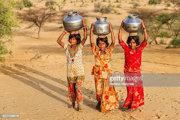 Indian little girls carrying on their heads water from well