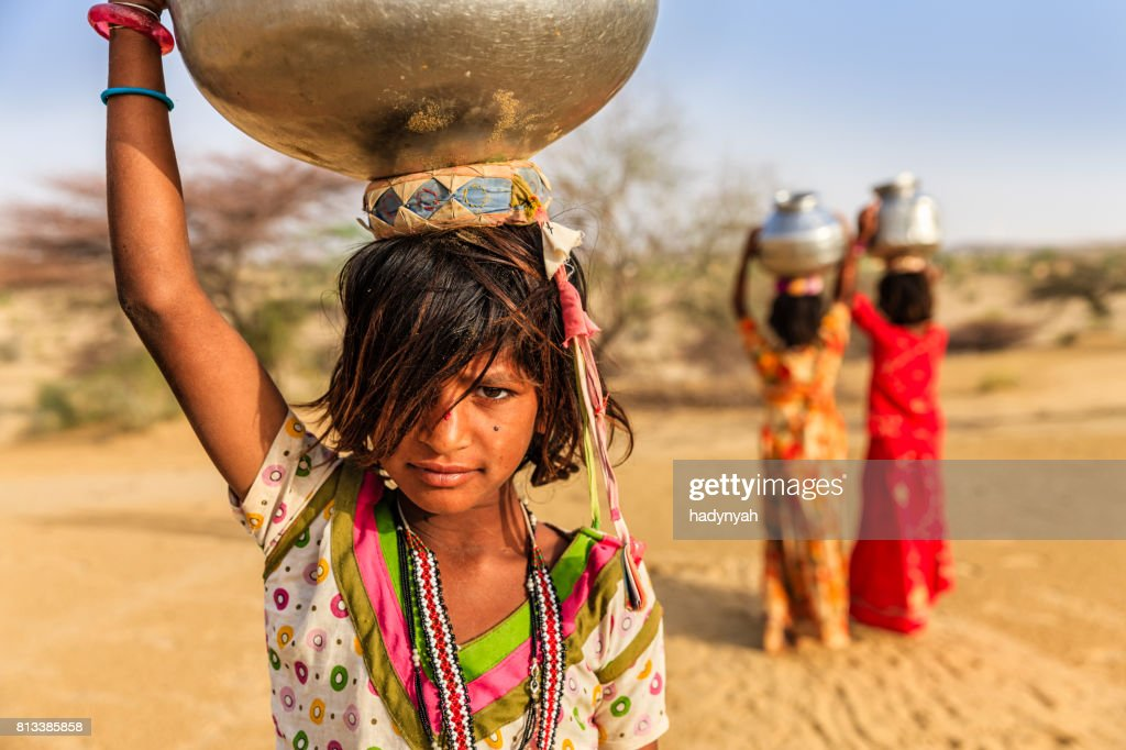 Indian little girls carrying on their heads water from well : Stock Photo