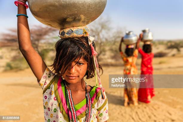 indian little girls carrying on their heads water from well - child labour stock pictures, royalty-free photos & images