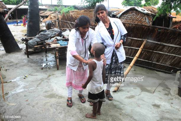 Indian local doctors checks the symptoms of AES to a child of Harvansh pur village vaishali District some 35 kms from MuzaffarPur Bihar on June 22...