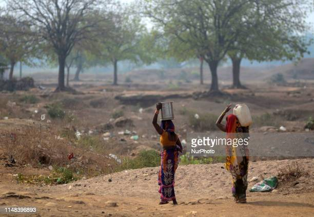 Indian local women return after carrying drinking water from a municaipal water tanker during a hot day in ShankarGarh Village , some 40 kms from...