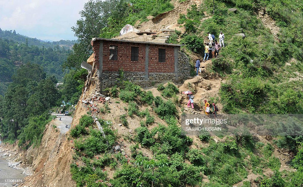 Indian locals make their way up the mountain as they bypass the washed out road next to the Mandakini river at Silli, in the flood affected area of northern Uttarakhand state on July 1, 2013. Construction along river banks will be banned in a devastated north Indian state amid concerns unchecked development fuelled last month's flash floods and landslides that killed thousands, the state's top official said July 1.