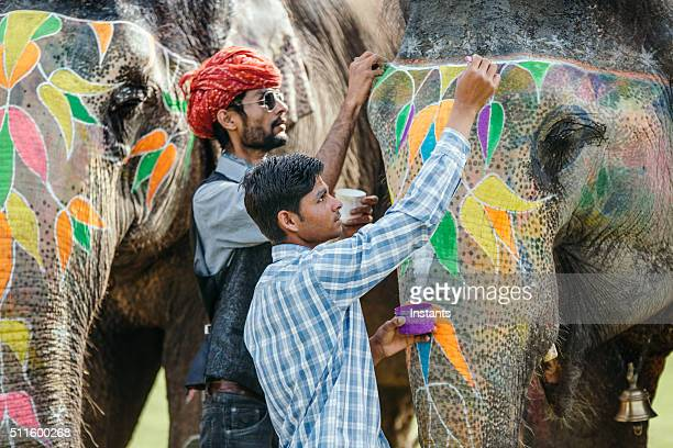 Indian mahouts decorating elephants