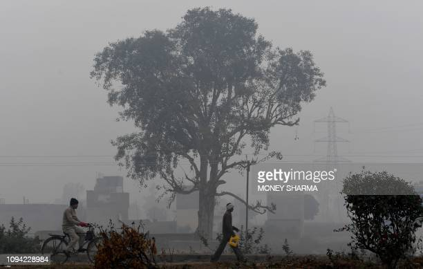 Indian make their way along a path amidst smog and fog conditions during a cold morning in Faridabad on February 6, 2019. - Smog levels spike during...