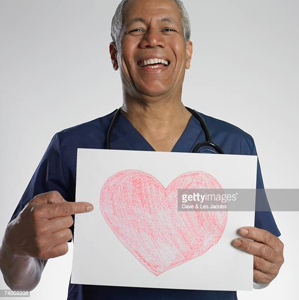 Indian male doctor holding heart drawing