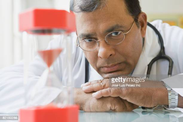 Indian male doctor looking at hourglass