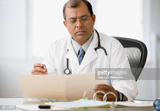 Indian male doctor reading chart