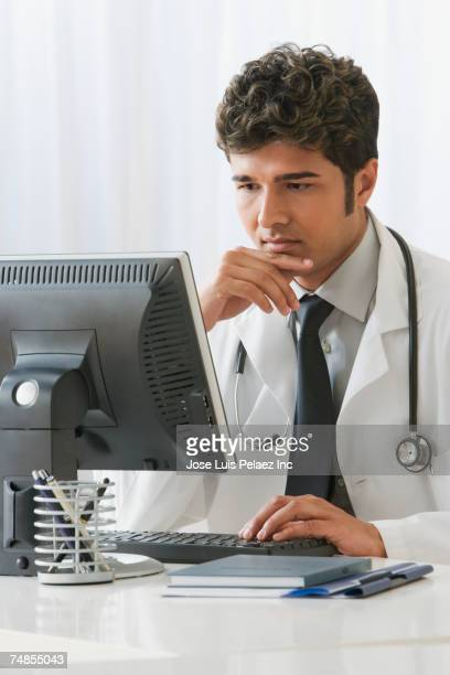 Indian male doctor typing on computer