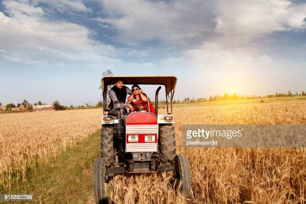 インドの男性・女性の農家においてトラクターの上に座って - ハリヤナ州 ストックフォトと画像