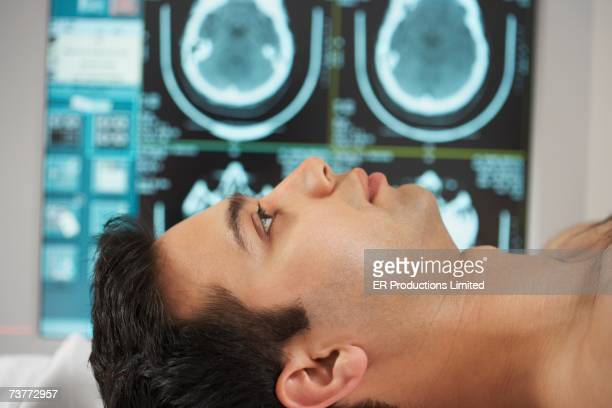 Indian male patient laying down with brain scans in background