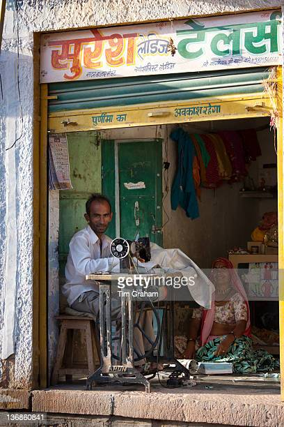 Indian man and wife sewing fabric in village of Rohet in Rajasthan Northern India