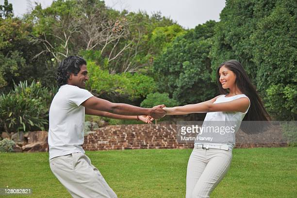 indian man and woman (25, 20 years old) holding hands and dancing in kirstenbosch botanical garden, cape town, western cape province, south africa - 25 29 years stock pictures, royalty-free photos & images