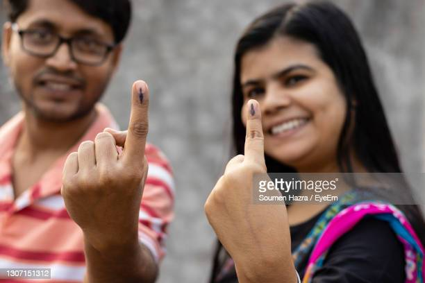 indian man and woman showing ink-marked fingers with smiling faces after casting vote - voting stock pictures, royalty-free photos & images