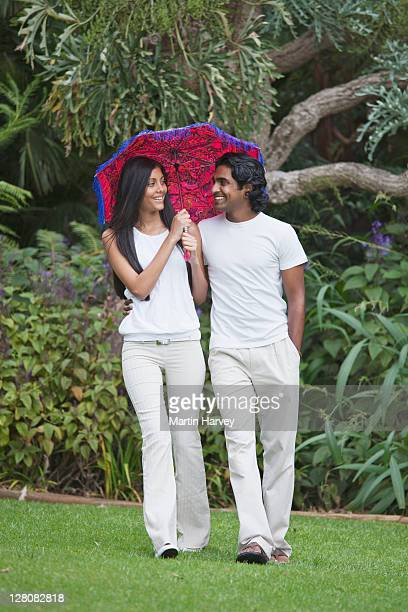 indian man and woman (20, 25 years old) strolling in the park with umbrella, kirstenbosch botanical garden, cape town, western cape province, south africa - 25 29 years stock pictures, royalty-free photos & images