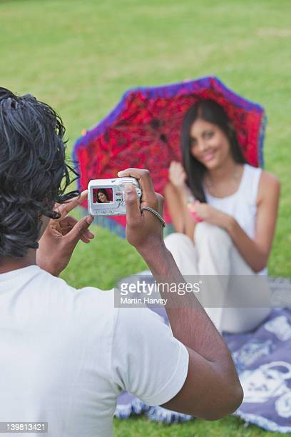 indian man and woman (25, 20 years old) using digital camera to capture memories in a park, kirstenbosch botanical garden, cape town, western cape province, south africa - 25 29 years stock pictures, royalty-free photos & images