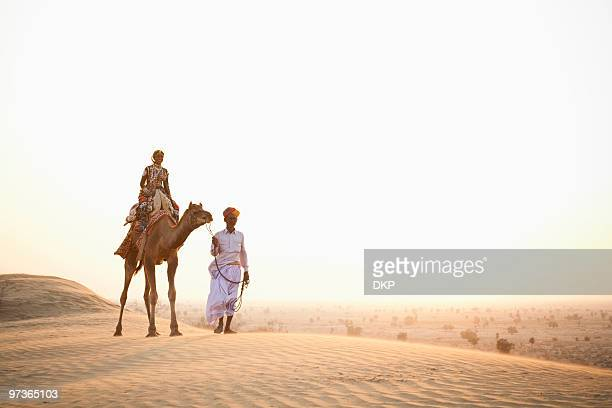 Indian Man and Woman with Camel In Desert